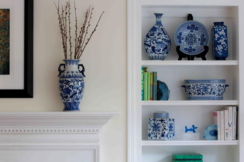 painted white wood trim mantel with blue and white vase and painted wood trim built-in-bookcase