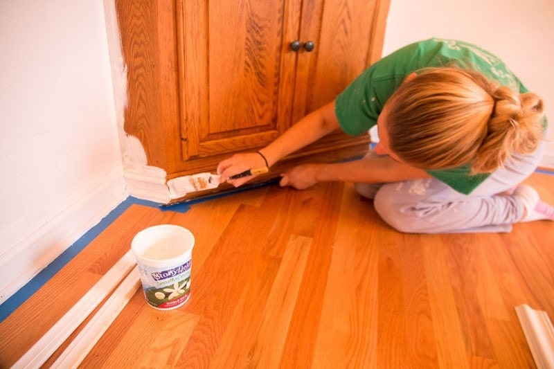 how to paint baseboards- woman painting baseboards white