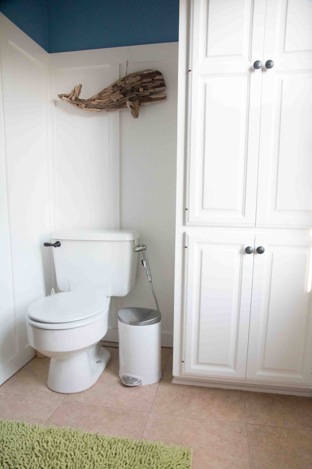 board and batten bathroom with white painted bathroom cabinets