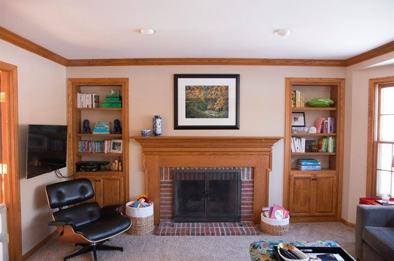 wood tone built in bookcases and brick fireplace