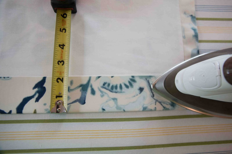 iron and measuring tape on ironing board smoothing DIY roman shades
