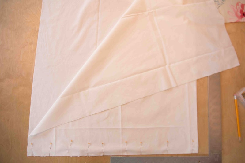 how to make roman shades with picture of fabric being stitched together with pins and a straight edge on table