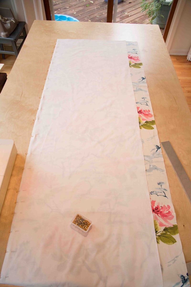making your own roman shade with fabric and fabric liner on a kitchen table with pins