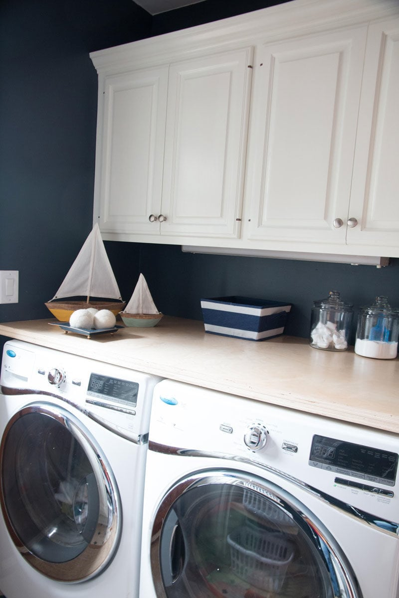 how to paint cabinets--navy blue laundry room and white laundry room cabinets with plywood countertop