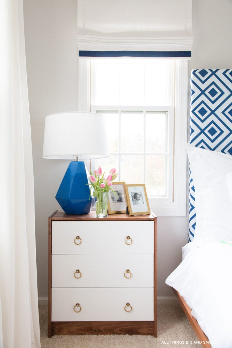 wood and white ikea bedside table with blue and white curtains and blue and white headboard