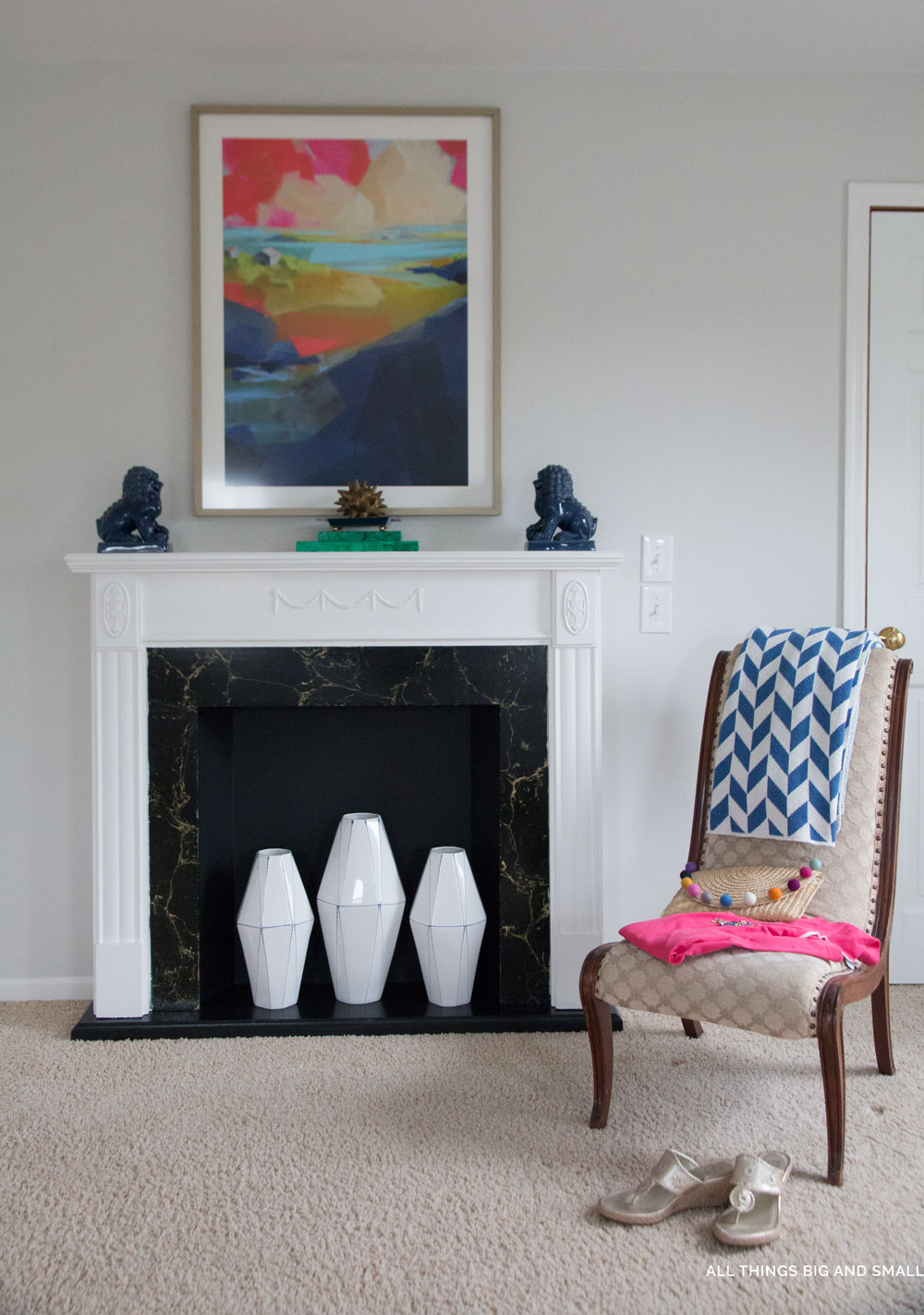 blue and white accents in a gray master bedroom with white fireplace