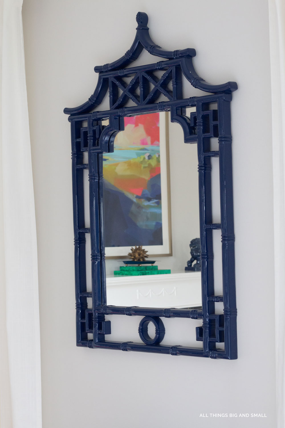 blue chinoiserie mirror on gray walls in blue and white master bedroom
