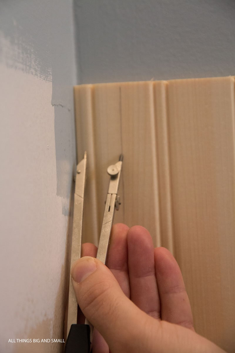 using a compass to scribe wood beadboard planks into uneven corner of bathroom