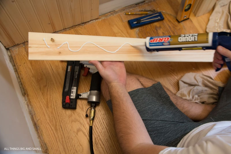applying liquid nails wood glue to the back of beadboard planks in beadboard bathroom