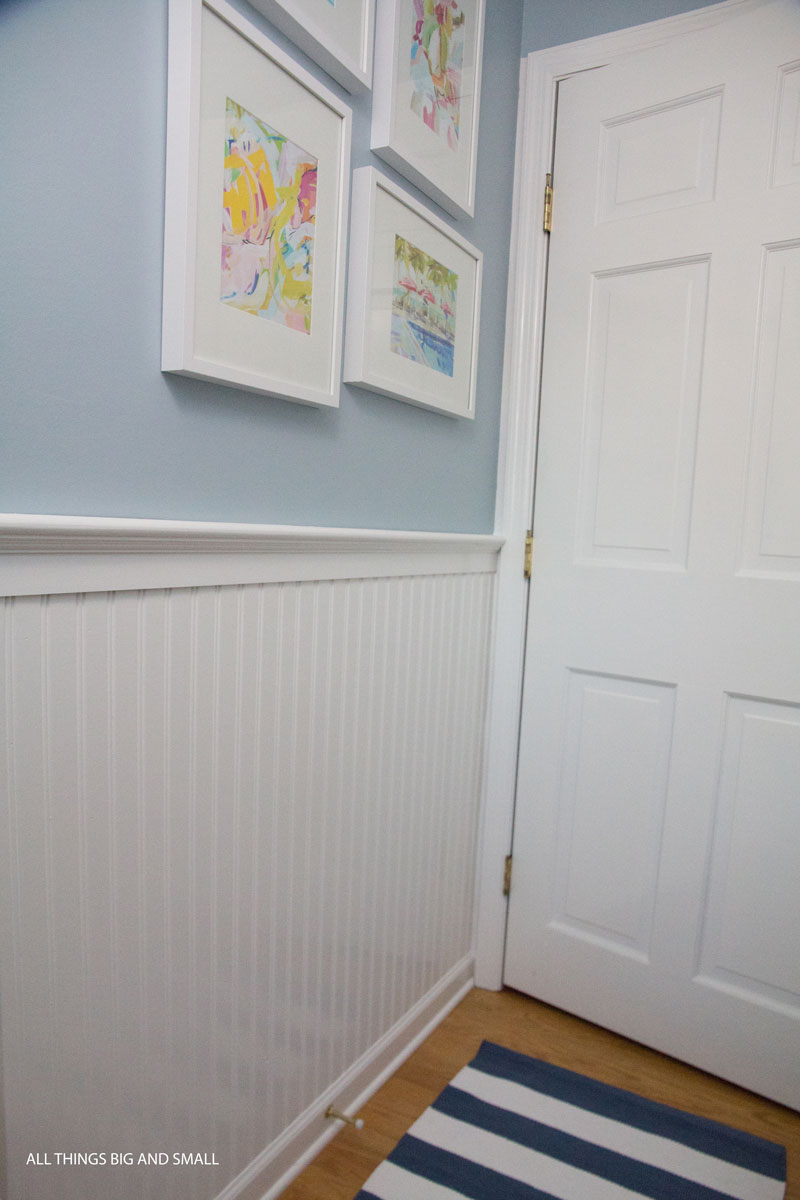 beadboard bathroom with blue walls and white beadboard