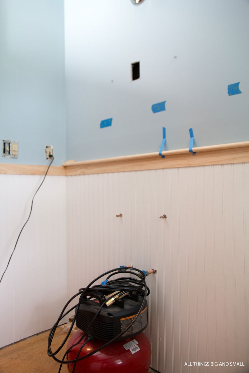 use painter's tape to hold trim pieces in beadboard bathroom to mock up prototypes