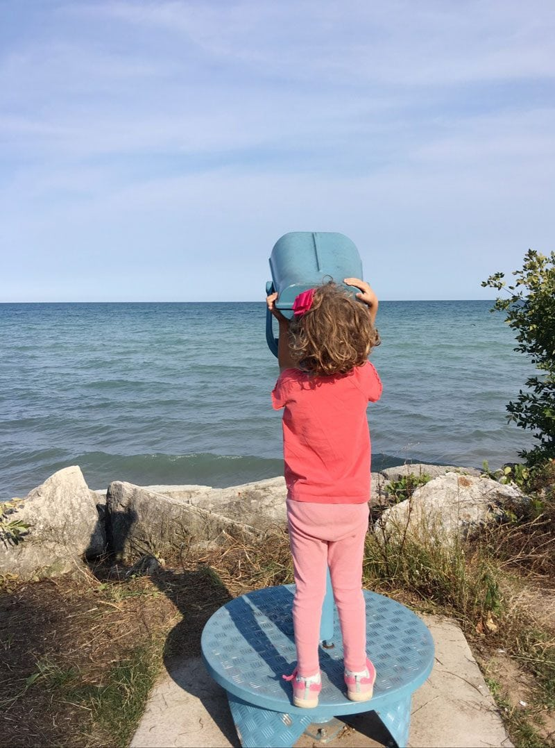 girl looking out of telescope--summer activities and schedule for kids that keep them busy