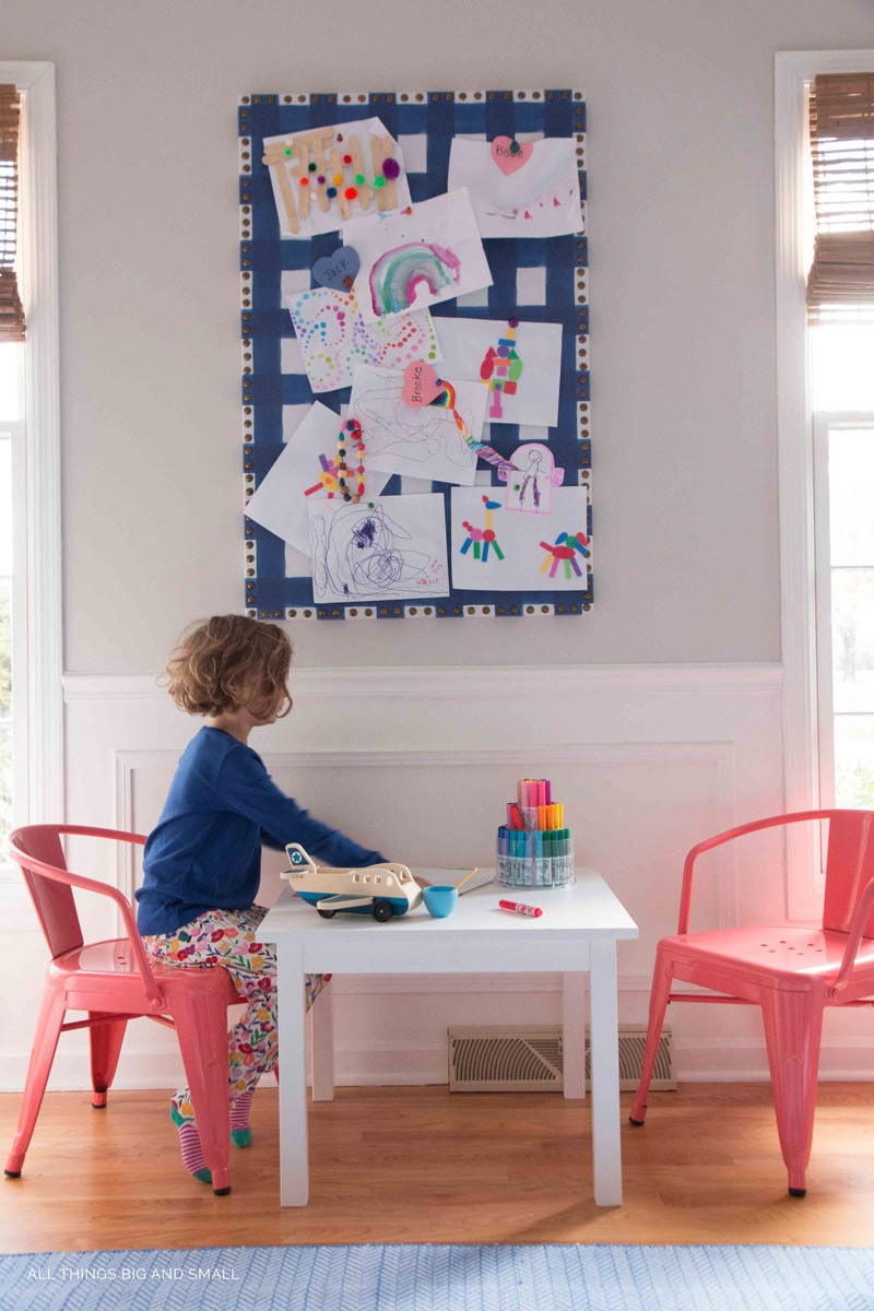 Girl drawing play table under kids art bulletin board in playroom decor makeover