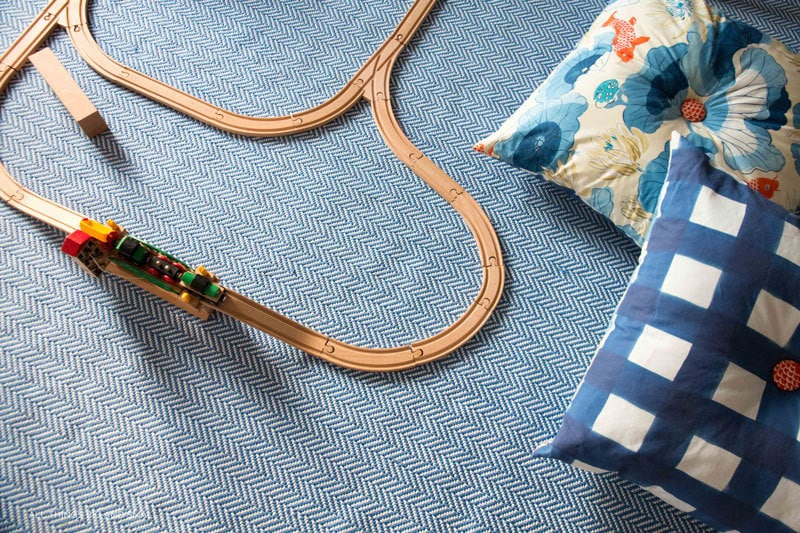 wooden train and DIY floor pillows on playroom rug--great playroom decor ideas for a playroom makeover