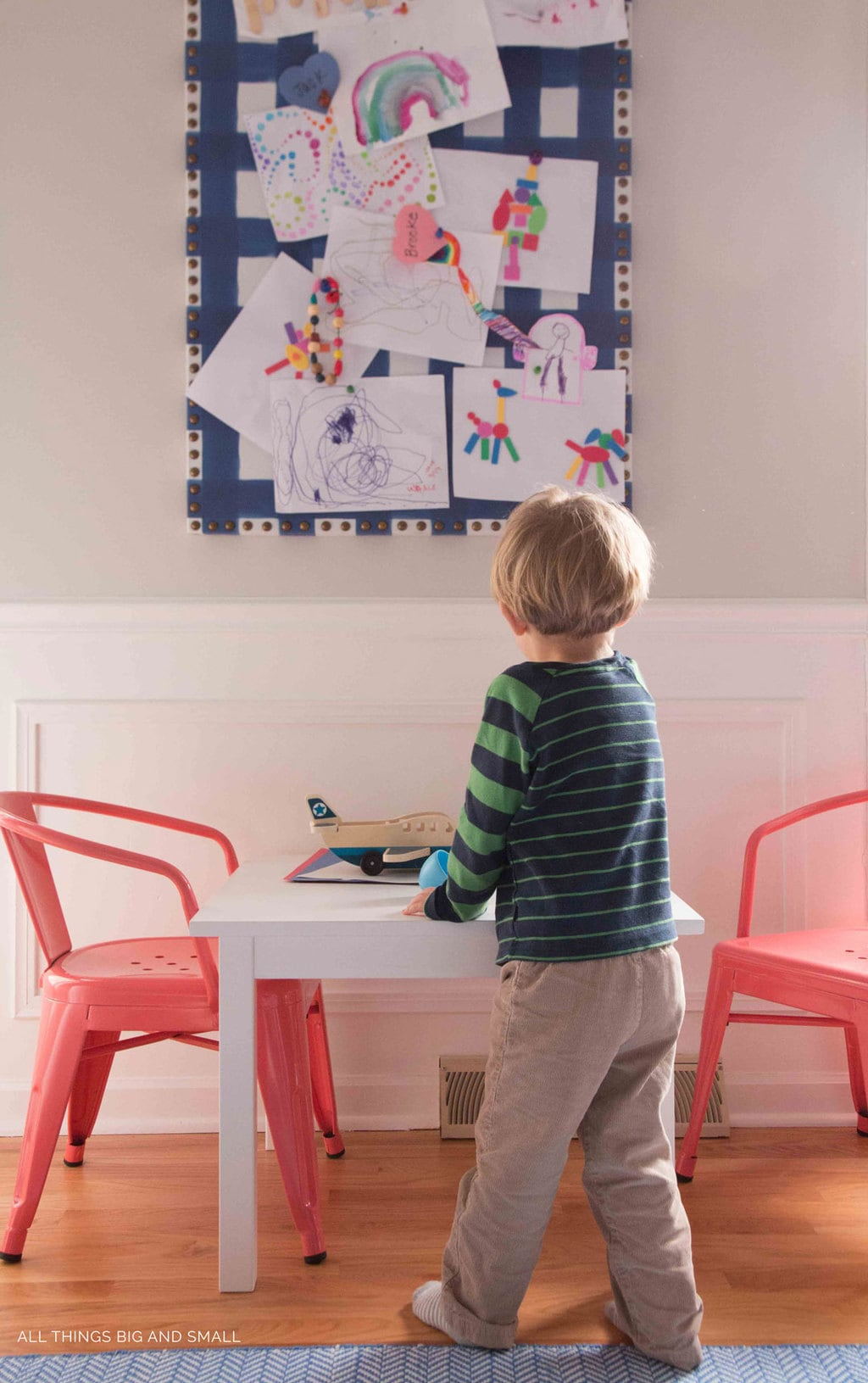 boy playing with wooden airplane in colorful playroom decor makeover