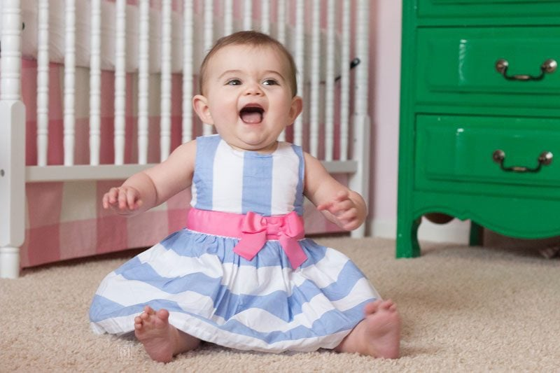laughing baby in a blue and white striped dress with big pink sateen bow from Carter's
