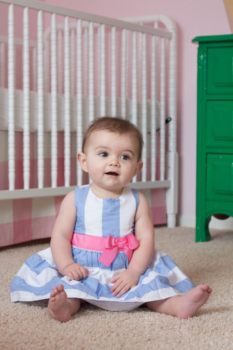 eight month old baby girl in blue and white striped dress with pink bow sitting in nursery