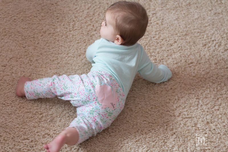 baby girl crawling on carpet in bunny pants and blue striped bodysuit from Carter's