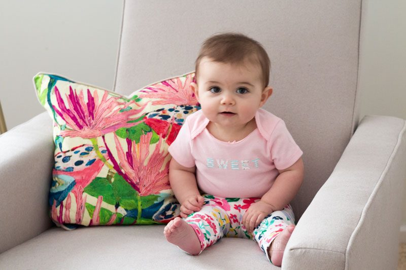 spring clothes for babies- short sleeve bodysuit and pants on baby girl sitting in glider