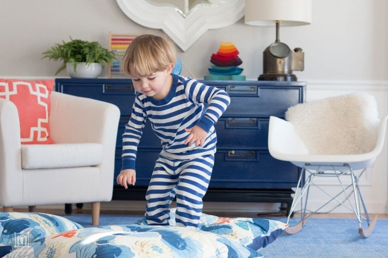 kid jumping on diy floor pillows in playroom decor makeover--the perfect playroom decor