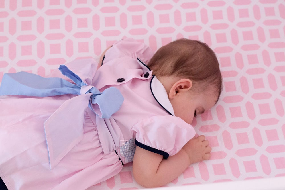 baby girl asleep in pink crib with smocked dress and blue bow