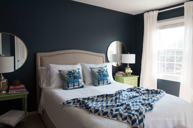 navy walls and blue and white bedroom with blue and white bedding and white curtains