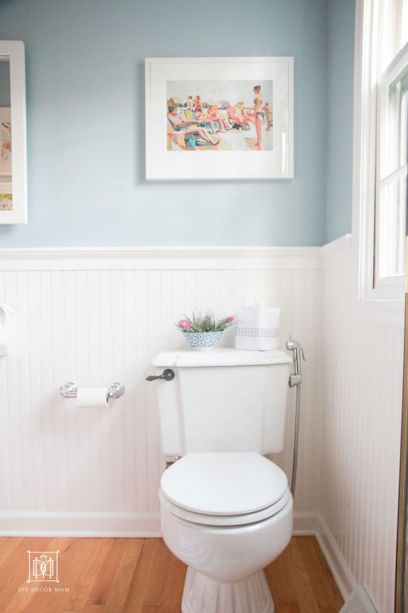 blue and white bathroom with white beadboard blue walls and white toilet
