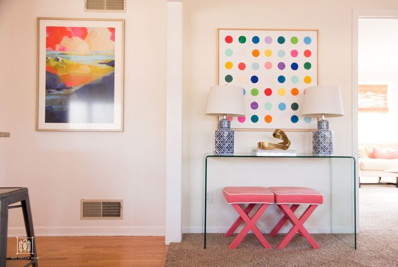 two abstract art pieces with glass console table decor