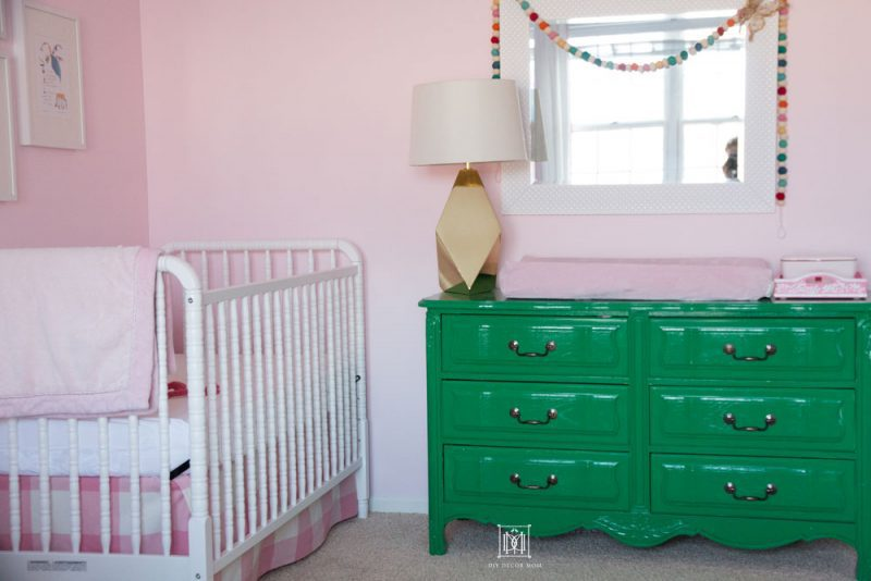 love this shared girls bedroom with a white crib and a green dresser in a pink nursery