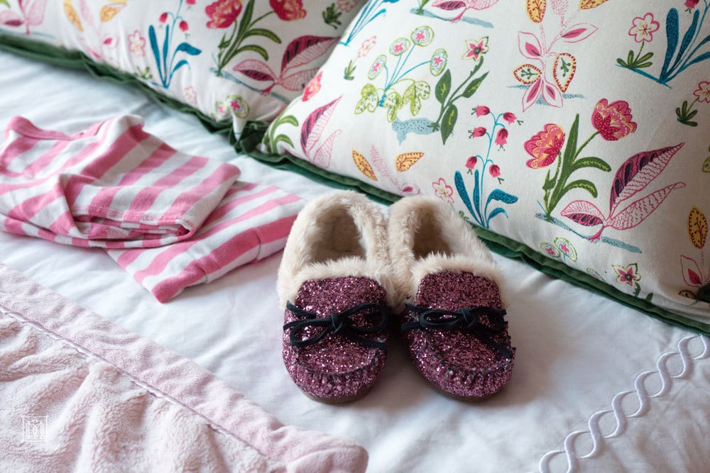 pink pajamas pink glitter slippers on girls bed in shared girls bedroom