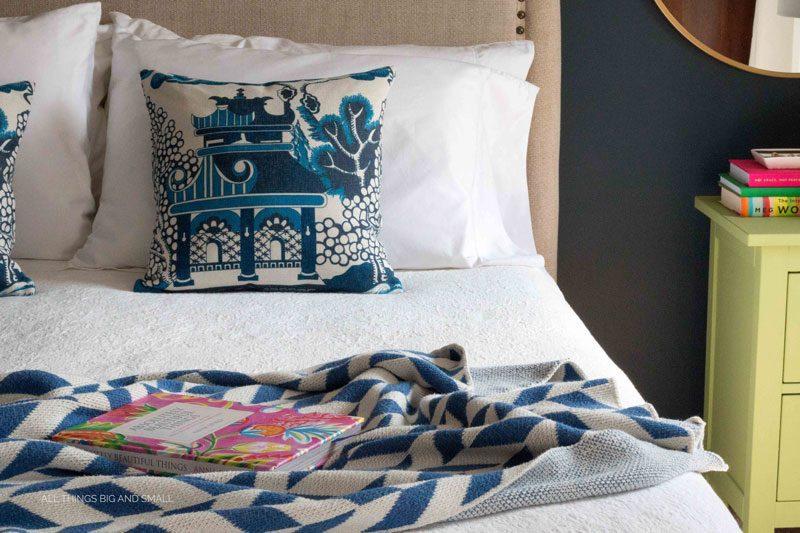 white bed with blue blanket in benjamin moore hale navy painted bedroom