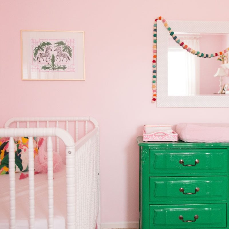 pink nursery with decorative garland and green dresser