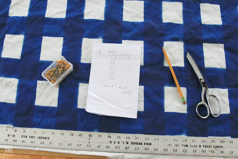 blue buffalo check fabric and ruler and pins for DIY fabric covered bulletin board