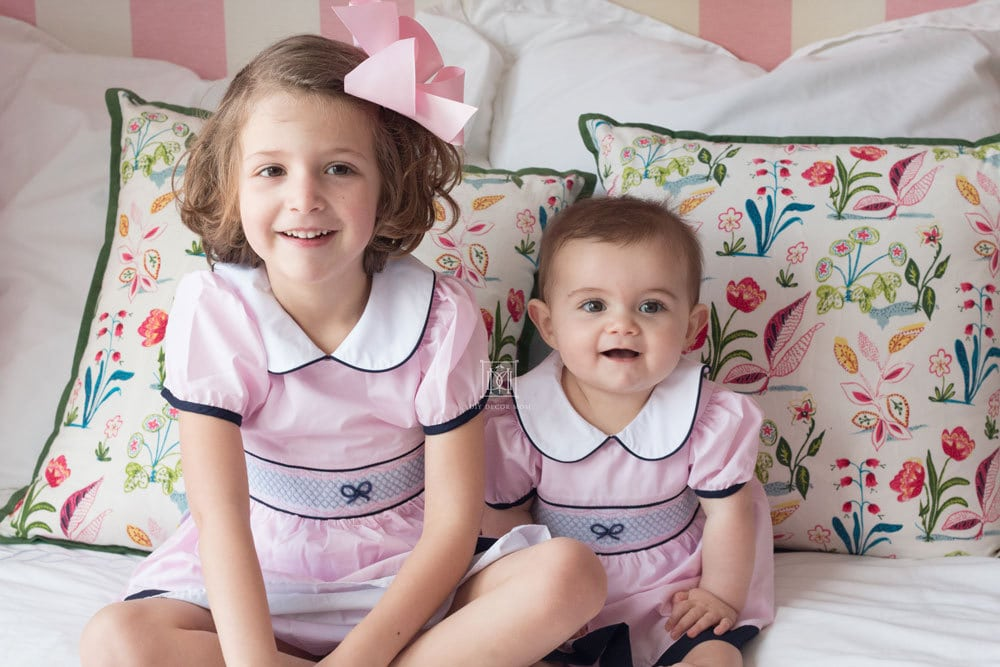 toddler and baby sister in pink smocked dresses on white bed in girls shared room