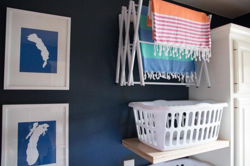 navy blue laundry room with nautical artwork turkish towels and floating shelves with laundry baskets with walls painted benjamin moore hale navy paint color