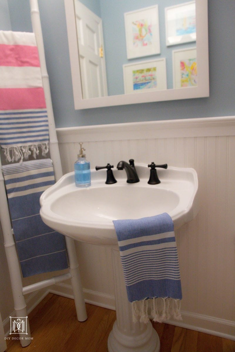 blue and white bathroom with pink turkish towels on bamboo ladder on white sink