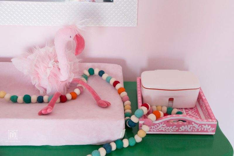 pink flamingo stuffed animal on top of pink changing mat on green dresser in pink girls shared bedroom