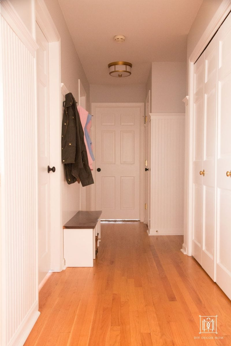 small mudroom in hallway entrance with beadboard