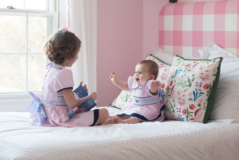 shared girls bedroom different ages baby and toddler on bed
