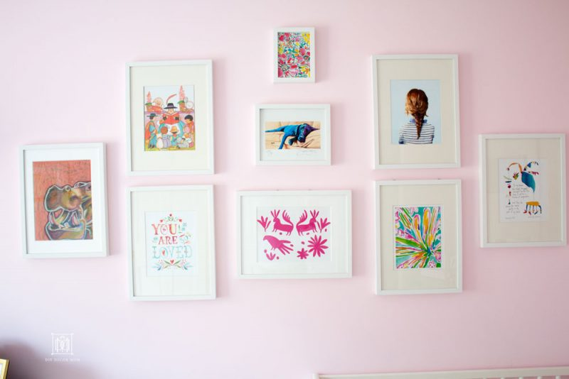 light pink wall color gallery wall in white frames in shared girls bedroom