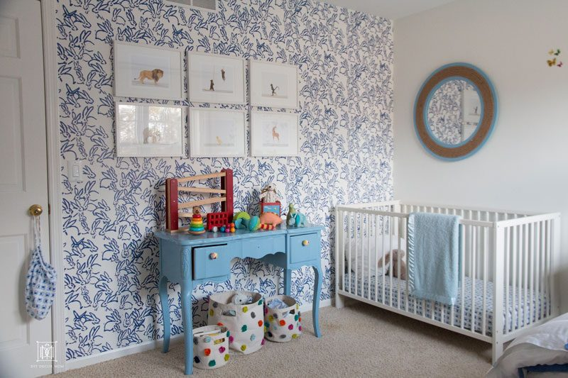 baby boy bedroom- blue and white wallpaper with white crib and blue mirror blue changing table