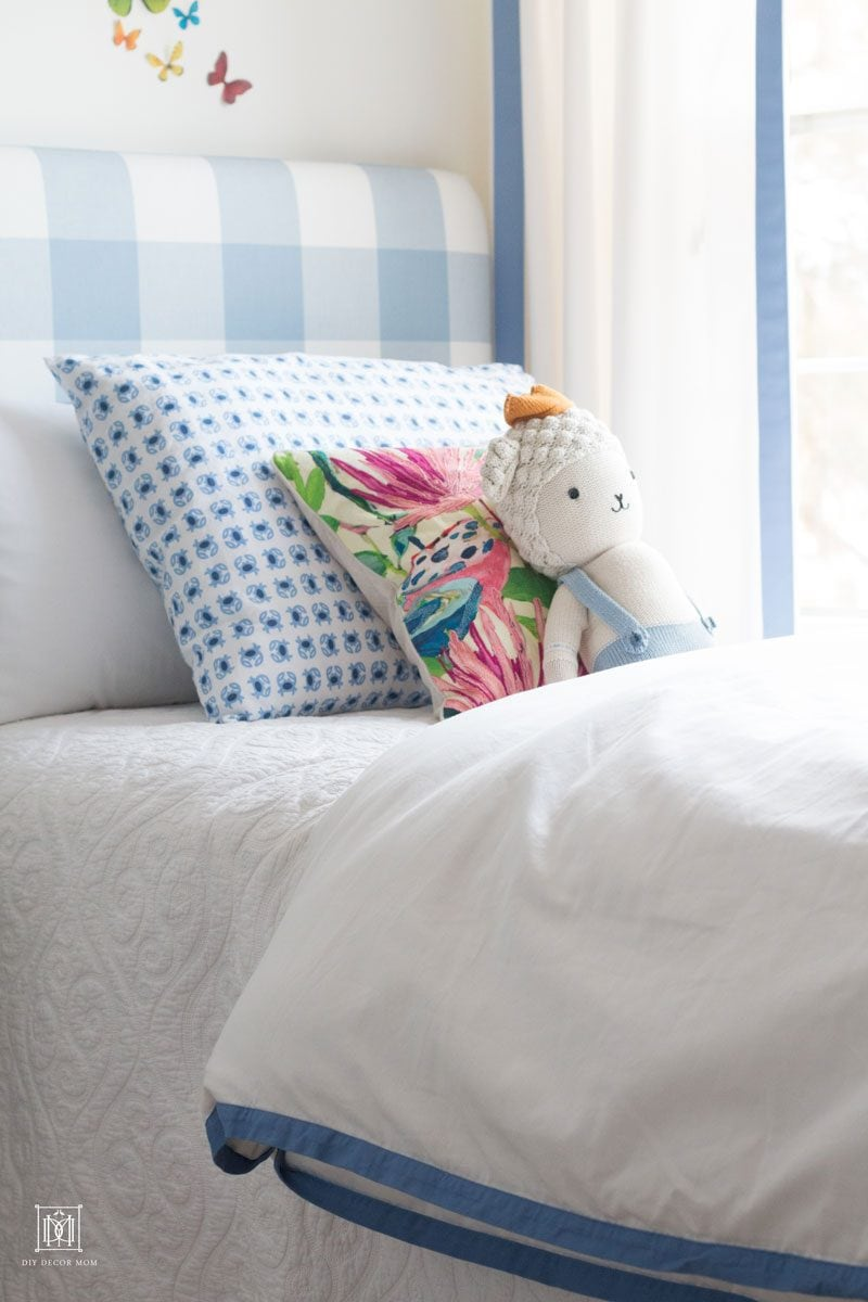 detail shot of blue and white buffalo check bed in front of DIY Curtains and cornice box