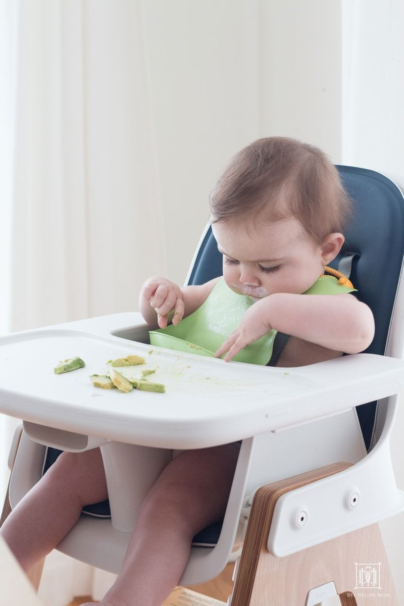 baby eating avocados in a easy to clean high chair