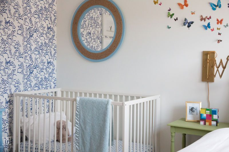 Blue and white wallpaper accent wall Ikea crib and butterfly wall decor in