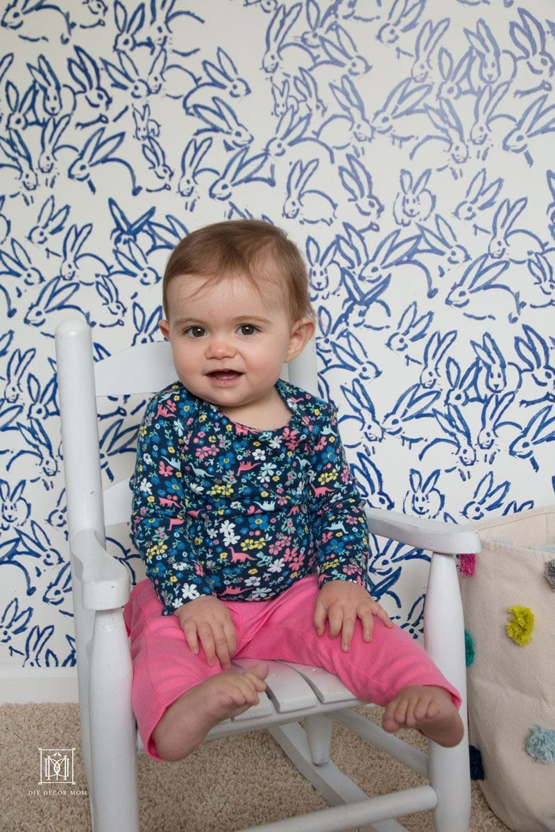 cute baby girl in blue and white nursery wearing blue bodysuit and pink baby pants