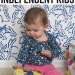 baby reading book while sitting on floor- new mom tips