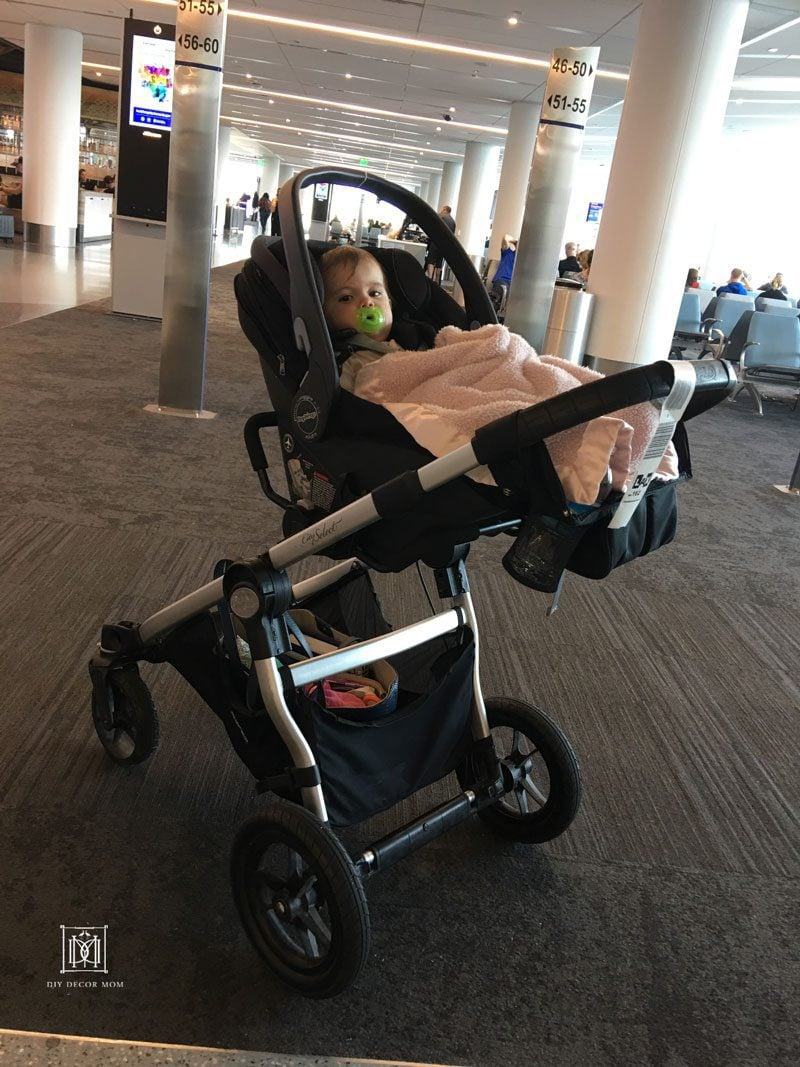 tips for flying with baby- baby in stroller at airport terminal