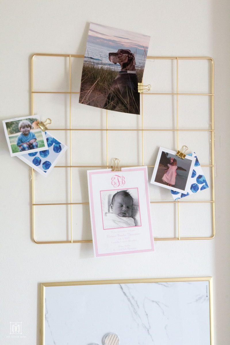 wire board with photos of children and birth announcements in family command center