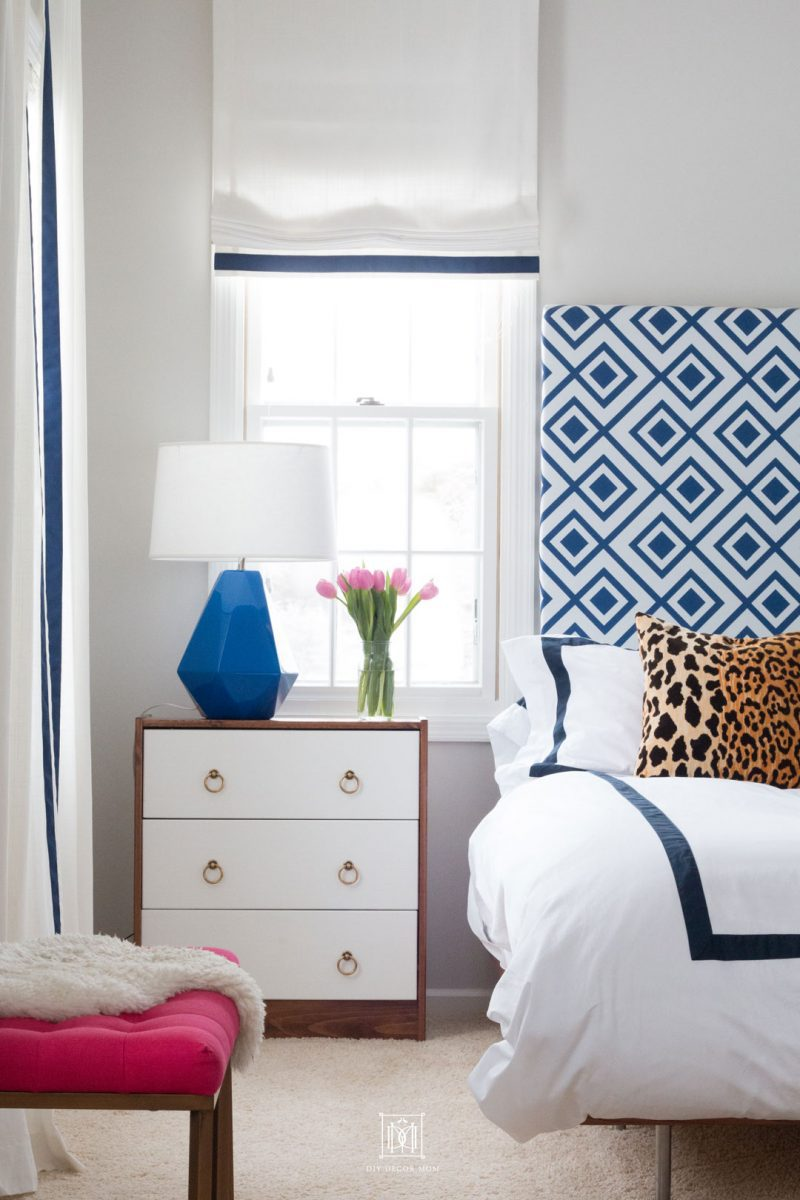 picture of blue and white bedroom with gray walls blue lamp, blue and white curtains and blue and white DIY headboard and leopard throw pillows