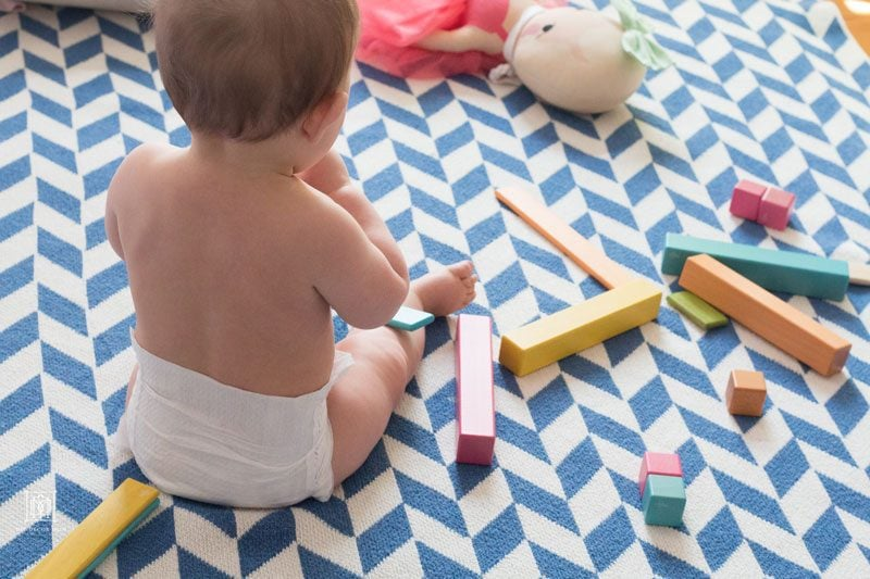 baby in diapers playing with wooden toys on blue and white blanket showcasing how to improve indoor air quality